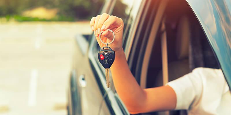 Woman Showing Car Keys Out Of Car Window
