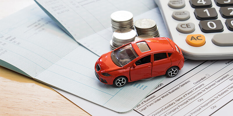 toy car and coins on insurance papers